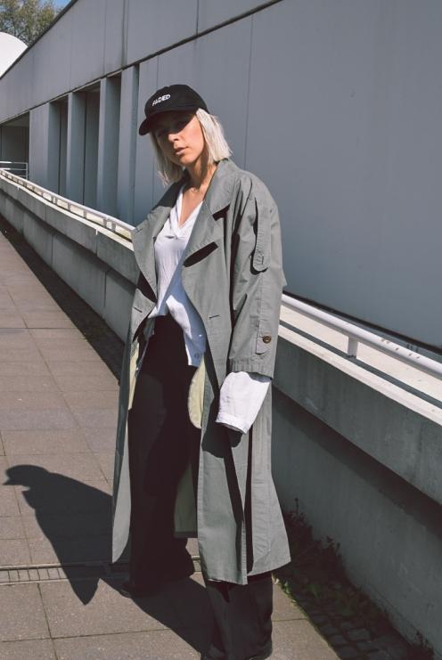 Outfitmerkmale: Leichte, dünne Stoffe, Übergroßes Hemd und Jacke, Ledertasche und -Schuhe, Cap.